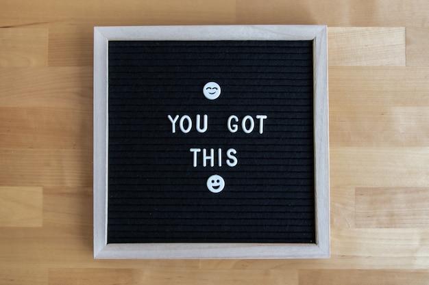 A foto da vista superior de um quadro-negro com você tem esta citação em uma mesa de madeira