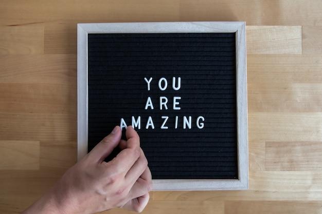 A foto da vista superior de um tabuleiro preto vazio em uma mesa de madeira com você é incrível