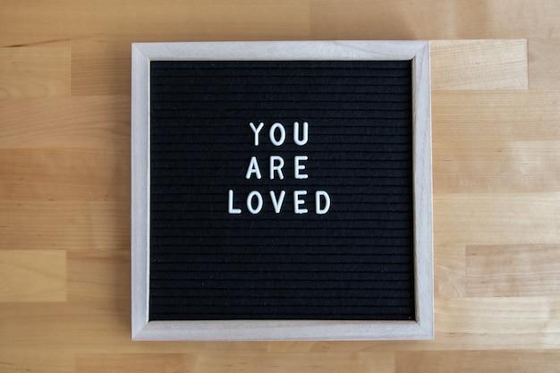 A foto da vista superior de um tabuleiro preto vazio em uma mesa de madeira com você é uma citação amada