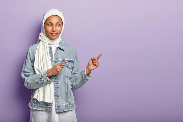 A foto de meio comprimento de uma bela mulher árabe indica de lado, sugere experimentar o produto do aplicativo, usa véu branco, jaqueta jeans stylsih