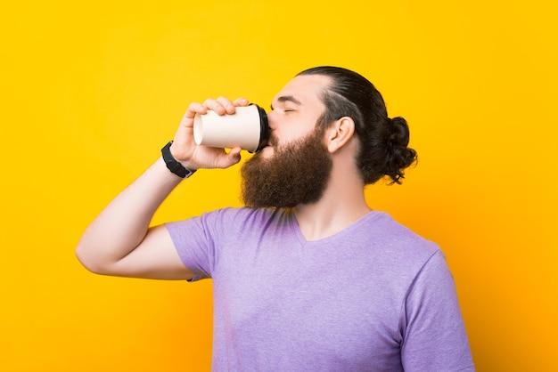 A foto de um homem barbudo saboreando seu café