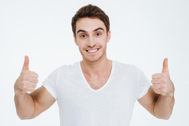 A foto de um jovem feliz vestido com uma camiseta branca em pé sobre um fundo branco faz o gesto de polegares para cima.