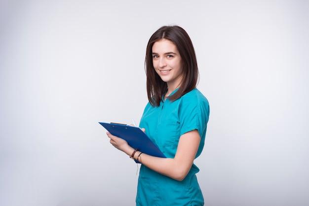 A foto de uma estudante jovem médica ou dentista está escrevendo algo em uma placa de papel azul.