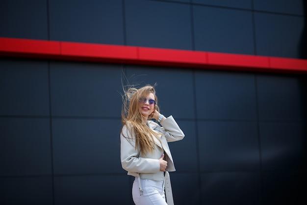 A foto de uma garota de cabelos compridos em uma blusa branca e calça jeans clara fica com um sorriso no fundo da parede cinza do edifício em um dia ensolarado de primavera.