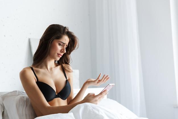 A foto de uma linda mulher confusa e descontente morena vestindo lingerie usando telefone celular encontra-se na cama.
