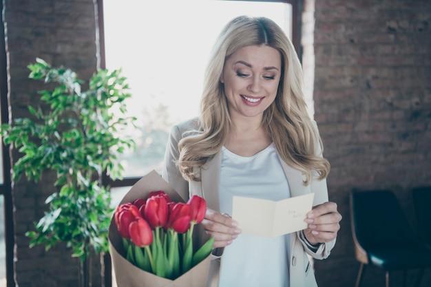 A foto de uma linda mulher de negócios veio segurando um pequeno cartão postal de tulipas