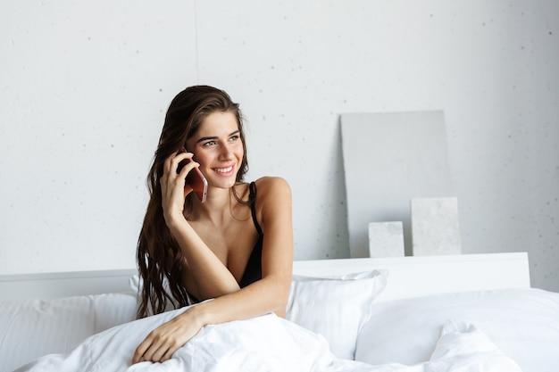 A foto de uma linda mulher morena feliz incrível vestindo lingerie, falando pelo celular, encontra-se na cama.