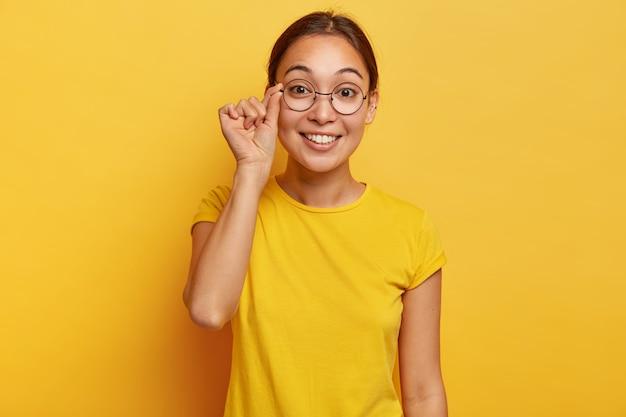 A foto de uma mulher atraente parece curiosa, tem uma expressão feliz, toca a moldura dos óculos, usa uma camiseta amarela, lê boas notícias, concentrada, posa dentro de casa. expressões de rosto humano