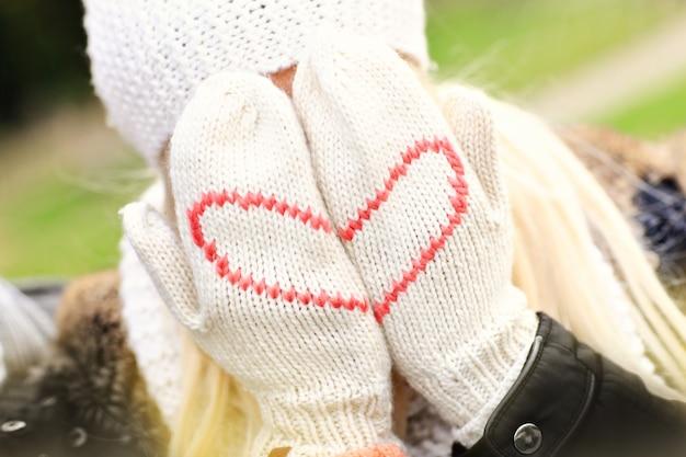 A foto de uma mulher cobrindo o rosto com luvas de inverno