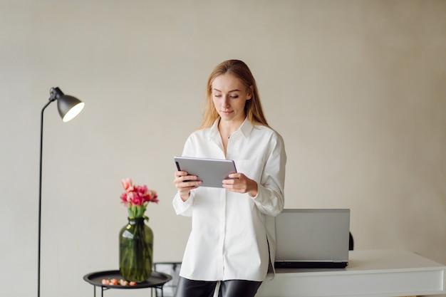 A foto de uma mulher de negócios loira jovem alegre no escritório dentro de casa trabalha com laptop e telefone celular.