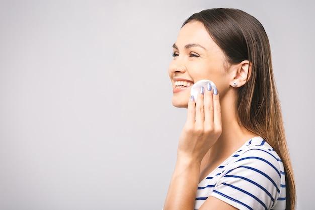 A foto de uma mulher feliz limpando o rosto com almofadas de algodão