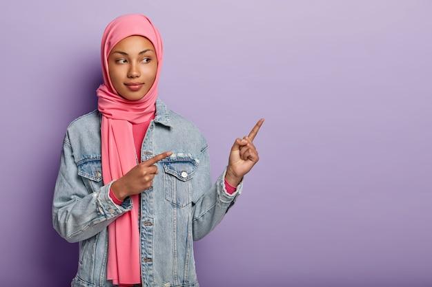 A foto de uma senhora árabe autoconfiante em um hijab rosa tradicional mostra o caminho certo, aponta para o espaço em branco com os dois dedos da frente, convida para ir lá, promove o espaço de cópia. verifique comigo