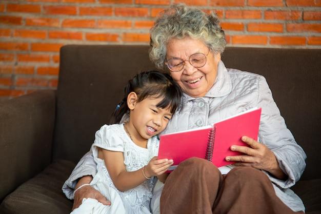 A foto do close up da avó ensina a ler um livro sua neta, conceito de família.