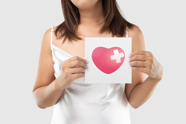 A foto do coração está no papel branco, dor de coração severa, ataque cardíaco ou cólicas dolorosas, doença cardíaca, pressionando o peito com expressão dolorosa.