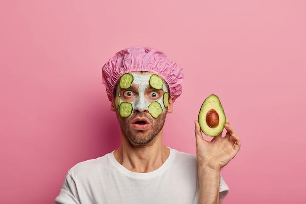 A foto do homem atordoado engasga de admiração, segura o abacate perto do rosto, surpreendido pelo efeito da máscara de argila, usa touca de banho, tem cerdas, isolado sobre a parede rosa do estúdio. beleza, bem-estar