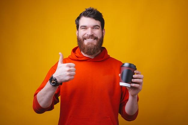 A foto do homem barbudo está segurando tira o copo. encomende o seu café online e fique em casa.