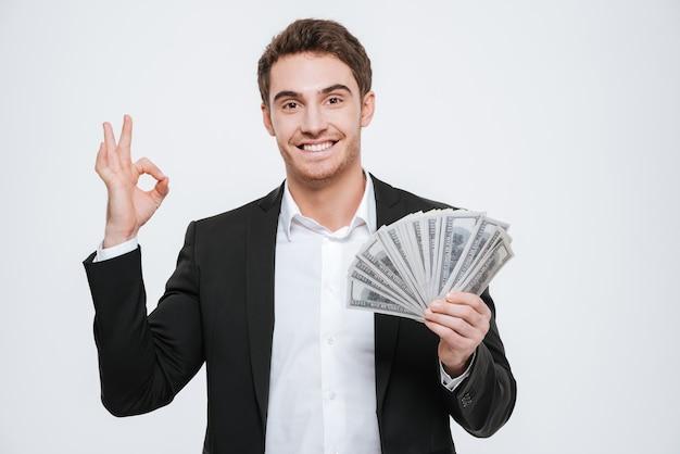 A foto do jovem empresário alegre em pé segurando dinheiro nas mãos faz um gesto de aprovação. isolado sobre a parede branca.