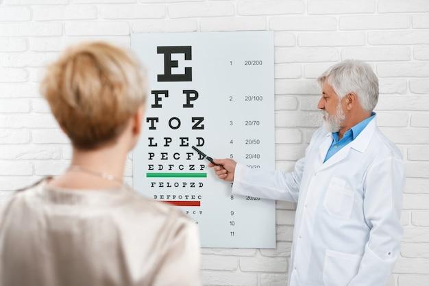 A foto do oftalmologista idoso está cheking a visão do paciente.