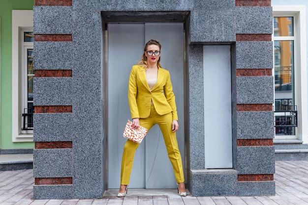 A foto em tamanho real de uma mulher de negócios em um terninho colorido e uma bolsa rosa. a modelo está posando para um fotógrafo perto da entrada do elevador.