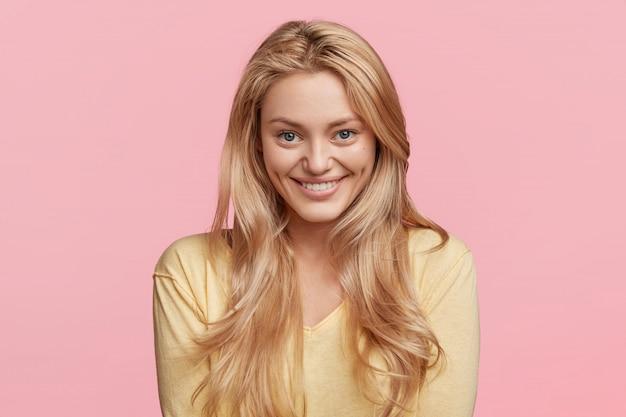 A foto horizontal da modelo feminina feliz e satisfeita com um sorriso agradável tem cabelo longo e reto, usa um suéter amarelo, fica feliz em receber uma boa posição de trabalho, posa contra a parede rosa emoções positivas