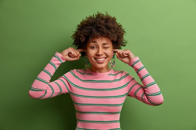 A foto horizontal de mulher feliz étnica tapa os ouvidos com os dedos, ouve música alta na festa, pisca os olhos e posa dentro de casa, vestida com um macacão listrado casual. mulher ignora barulho vindo dos vizinhos