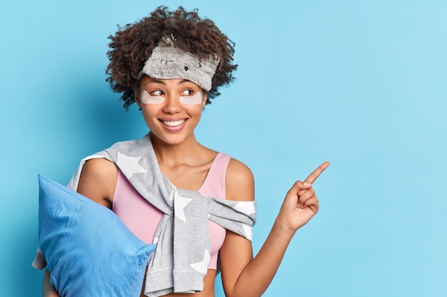 A foto horizontal de uma alegre garota étnica em roupas de dormir sorri positivamente indica que no canto superior direito segura o travesseiro demonstra o produto para descanso isolado sobre a parede azul