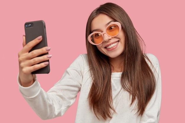 A foto horizontal de uma linda garota de cabelos escuros sorri feliz, inclina a cabeça, segura o celular, grava o vlog, tira uma selfie, usa óculos escuros da moda e suéter branco casual, isolado sobre a parede rosa