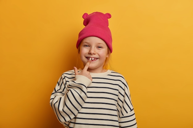 A foto horizontal de uma menina muito pequena indica seu novo dente, se preocupa com os dentes, usa roupas elegantes, tem uma expressão engraçada, ri dentro de casa, isolada sobre uma parede amarela brilhante