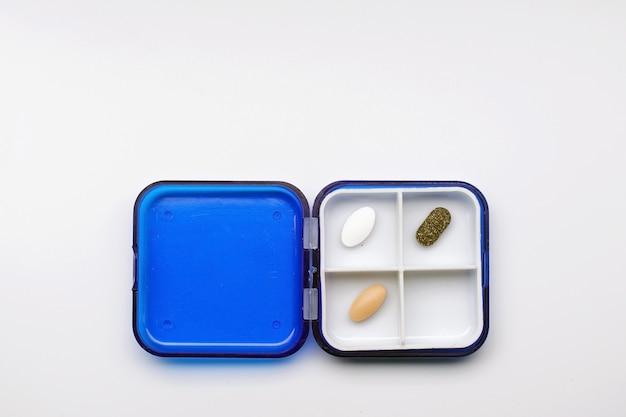 A foto mostra uma caixa com diferentes cápsulas e comprimidos