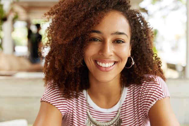 A foto na cabeça de uma linda mulher de pele escura com expressão feliz tem penteado afro, demonstra dentes perfeitamente brancos e uniformes, tem sorriso satisfeito. jovem afro-americana elegante descansando em uma casa