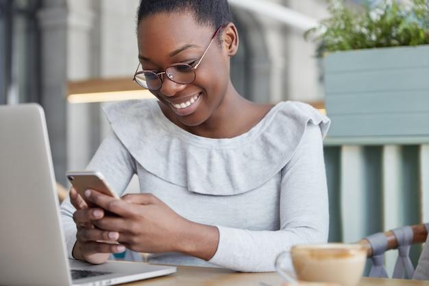 A foto recortada de um redator feminino satisfeito lê informações positivas no telefone inteligente, senta-se em frente a um laptop aberto e bebe café aromático.