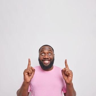 A foto vertical de um homem adulto barbudo bonito com pontas de barba espessa acima com os dois dedos indicadores mostra que o espaço para o conteúdo da sua publicidade parece felizmente suspenso sobre a parede cinza