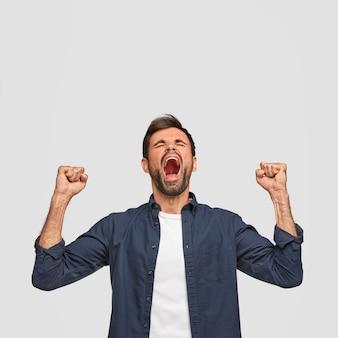 A foto vertical de um homem de sucesso tem uma expressão de alegria, fecha os punhos e abre a boca amplamente, exclama de felicidade, vestido casualmente, isolado sobre a parede branca com espaço de cópia para cima