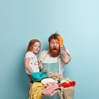 A foto vertical de um homem vermelho estupefato confundiu a expressão facial, abre a boca amplamente, passa o tempo em casa com uma pequena filha, faz as tarefas domésticas, não consigo decidir por onde começar isolado no azul