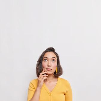 A foto vertical de uma jovem asiática pensativa e sonhadora com cabelo escuro focado acima considera que algo usa um macacão amarelo casual isolado sobre o espaço de cópia de parede branca para seu anúncio