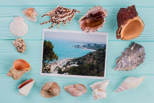 A fotografia com o mar está rodeada por diferentes conchas do mar. mesa de madeira azul.