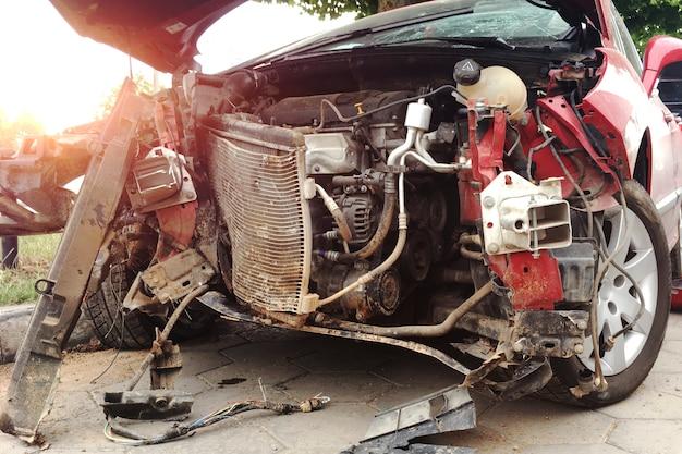 A frente de um carro vermelho sofreu um acidente na estrada.