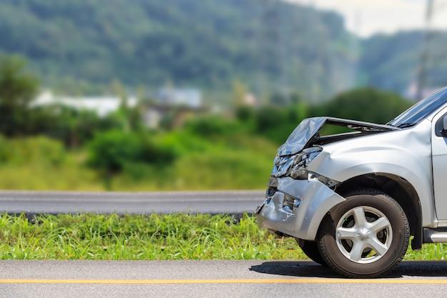 A frente do carro prateado é danificada por acidente na estrada