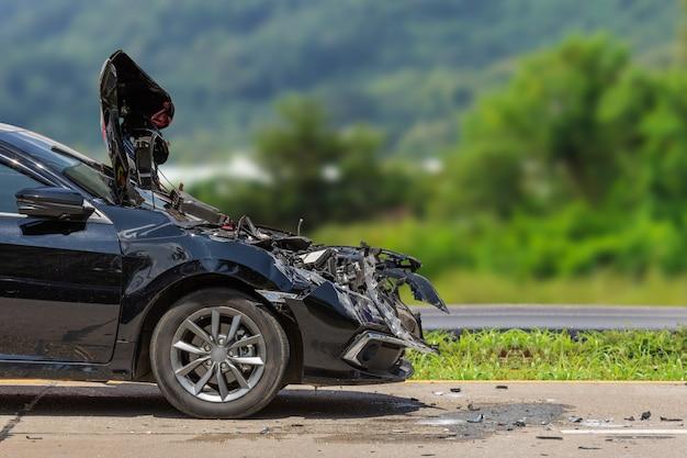 A frente do carro preto é danificada por acidente na estrada