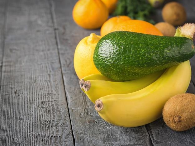 A fruta é verde, abacate maduro, três bananas e outras frutas tropicais em uma mesa rústica.
