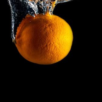 A fruta laranja cai na água com um respingo