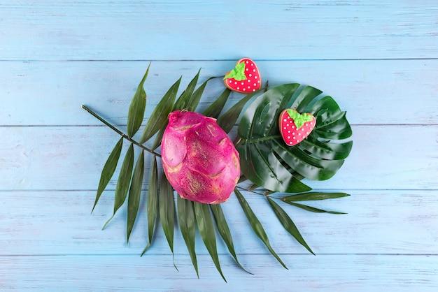 A fruta tropical do dragão com as cookies vitrificadas caseiros serviu nas folhas de palmeira no fundo de madeira azul.