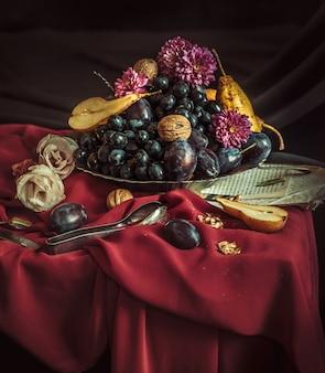 A fruteira com uvas e ameixas contra uma toalha de mesa marrom