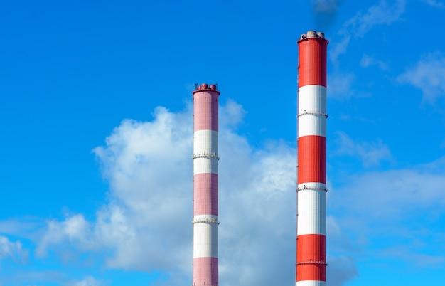 A fumaça das chaminés contra o céu azul com nuvens