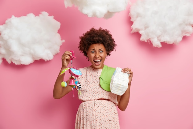 A futura mãe emocional grita emocionalmente, segura a fralda e o móbile do bebê, se prepara para o nascimento da criança, usa um vestido, se prepara para o chá de bebê, posa contra a parede rosa, nuvens brancas no alto