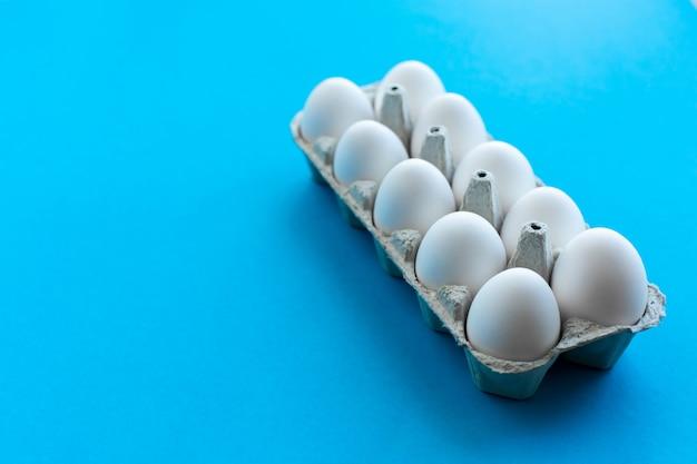 A galinha branca eggs em uma caixa de cartão aberta em um fundo azul. uma dúzia de ovos em embalagens ecológicas