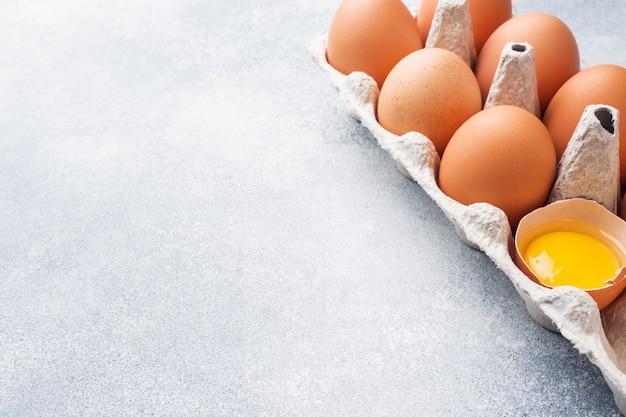 A galinha crua de brown eggs na fábrica que empacota no fundo cinzento. espaço da cópia