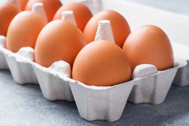A galinha crua de brown eggs na fábrica que empacota no fundo cinzento.