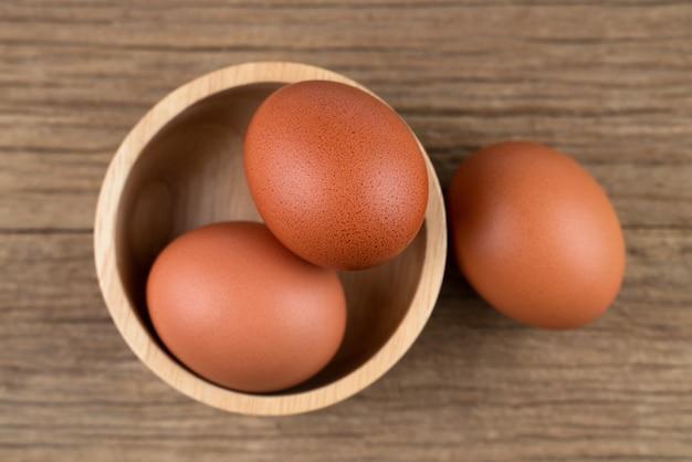 A galinha crua eggs o alimento biológico no fundo de madeira rústico