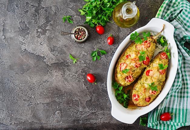 A galinha da carne e os vegetais triturados encheram beringelas em um fundo cinzento.